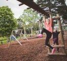 Girl-on-adventure-playground-monkey-bars